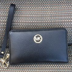 Black leather wallet Beautiful black wallet, extra storage for enough credit cards, can hold your phone as well. Zipper opens all the way around which is why I love this wallet, it's easy to get to all your things. Michael Kors Bags Wallets
