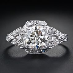 1.55 Carat Art Deco Diamond Engagement Ring. This glorious original Art Deco engagement ring, circa 1920s-1930s, highlights a bright and brilliant European-cut diamond weighing 1.55 carats. The beautiful gem stone is embellished on all four sides by small sparkling diamonds. The shoulders of the ring are designed in a stylized buckle or stirrup motif followed by tapered hand-engraving. A simply gorgeous vintage platinum and diamond engagement ring. Via Lang Antique & Estate Jewelry.