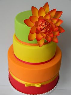 Tiered cake in awesome warm colors of apple green, bright orange, and deep red. ~ trish