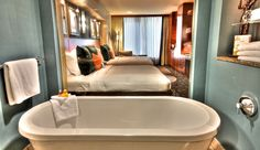 """It is this awesome.  I stayed there two years ago and fell in love with the tub.  The bath includes a glass surround shower and a free-standing two-person """"fill from the ceiling"""" pedestal tub. A glass wall joins bath and bedroom, while an electronic shade allows for privacy between the two.    Hotel 1000, Seattle, WA."""