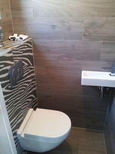 """(Welbie Sanitair) Denkend aan de vakantie in Afrika .....  Toilet met """"Hout"""" tegels op vloer en wanden, Zebra tegels op achterwandje. Meer informatie voor eigen badkamer ontwerp op www.welbie.nl"""