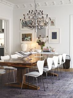 Eclectic dining room, white walls, white modern chairs, wooden table, faded traditional rug, black chandelier