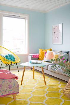STUEN: - Den blomstrete puffen har fulgt meg i ti år. Det vi hadde fra før, måtte også passe inn i huset, sier Julie. Sofaen er fra Bohus, og putene er fra Oyoy, Kremmerhuset, Ferm Living og Hay. Den gule kurvstolen er kjøpt hos Åhléns, mens gulvteppet er fra Ikea. Bordet er fra Søstrene Grene. FOTO: Nadya Norskott