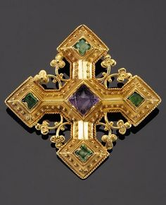 A GOTHIC REVIVAL GOLD BROOCH SET WITH GEM STONES, by Messrs John Hardman & Co., the design attributed to A.W.N. Pugin, circa 1860. In the form of a Gothic cross of gold centered with an amethyst, each axis terminated with an emerald.