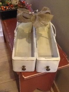 Two old sewing machine drawers, screwed together, added a handle from an old basket, painted and distressed and finished with a burlap bow.