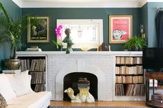 The fireplace with shelves, typical of Logan Square apartments, is filled with their collection of records and books. The original stained glass window is flanked with prints by two favorite artists, Jean Cocteau and Piero Fornasetti, purchased at Jean Cocteau's home at Milly-la-Foret and the Fornasetti exhibit in Paris.
