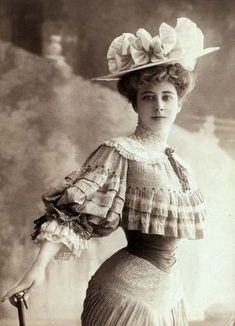 This's the typical garment of the 1900s. There're many big flowers on her hat…