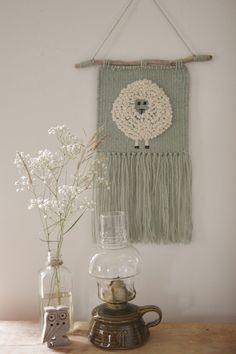 Embroidered Sheep Sheep woven wall hanging in soft sea-foam green and off-white wool yarn. This whimsical fluffy sheep would be perfect for a nursery or