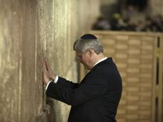 Canadian Prime Minister Stephen Harper touches the Western Wall, Judaism's holiest site in Jerusalem's old city on January 21, 2014.