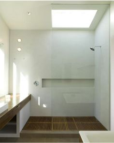 White bathroom with large shower, glass partition and wood pan, long vanity