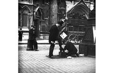He was one of a small number of photographers working in the late 19th century    who concentrated on the 'everyday', fascinated by the bustle of unposed life    around him. 	   A bootblack at work in a London street, c.1900