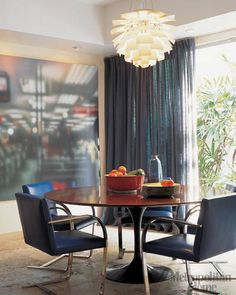 This breakfast area, by designer Andrew Frank, relies on modernist classics, including a rare wood-topped Saarinen table, Brno chairs by Mies van der Rohe and a hanging Artichoke pendant lamp by the Danish designer Poul Henninghsen. The acrylic painting is by the Irish artist Martin McGinn.    - ELLEDecor.com