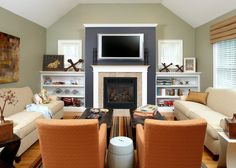 This neutral living room earns a spacious look as a result of its vaulted ceiling. The fireplace is positioned in front of a charcoal accent wall, adding a bold touch, while two neutral sofas and orange upholstered armchairs provide plenty of seating. A white built-in bookshelf is place on either side of the fireplace.