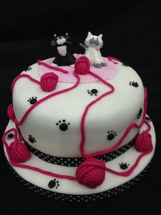 Cat cake with 2 fondant cakes on rug with balls of wool and paw prints