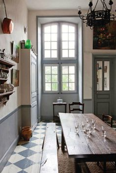 Beautiful light traditional kitchen in Southern France with a vintage wooden table and painted chequerboard wooden floor