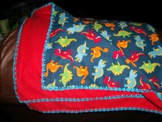 Baby blanket with crocheted edge with baby dinosaurs.