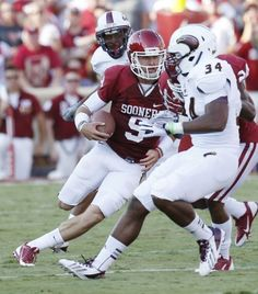 Oklahoma quarterback Trevor Knight (9)cuts between Louisiana Monroe defenders Darius Lively, left, and Michael Johnson (34) as he carries in the first quarter of an NCAA college football game in Norman, Okla., Saturday, Aug. 31, 2013. Photo: Sue Ogrocki