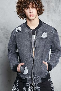A denim bomber jacket featuring an acid wash, a distressed design, pull-ring zip front closure, slanted front pockets, long sleeves, and contrast ribbed knit trim.
