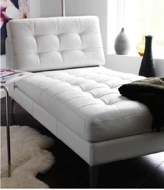 white leather Karlstad IKEA chaise lounge with metal legs.