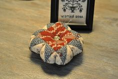 David's cottage down the hill.: A pincushion and a stitched pouch.