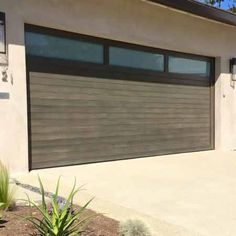 double cars mid century modern garage doors with wood material and windows on top plus wall scones and white wall and concrete floor