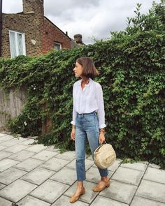 Denim, flats, and a white button down with embellishments.