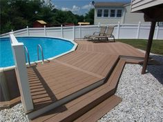This above ground pool is built uneven ground, and uses that to extend a deck from flat ground to the lip of the pool. This is a very clever way to integrate the above-ground design and make it feel like an in-ground pool.