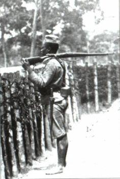 Soldado nativo de guarda à paliçada de um forte na fronteira do Rovuma, Moçambique.
