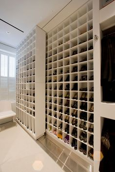 Beautiful walk in closet designs like this are every shoe-lover's dream come true. It takes advantage of high-tech  motion hardware, enabling you to efficiently maximize space. There are two rows/layers of shoe shelves, the smaller of which has top and bottom sliding runners, which you can use to move it side by side to access other shoes. The rest of the closet also has modern styling, with open hanging racks painted in plain white.