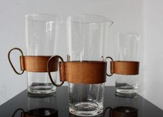 Leather and glass pitchers by Carl Aubock