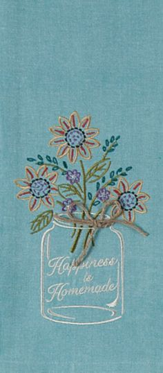 "Embroidered Chambray Tea Towel with Mason Jar Design. Embroidery saying: ""Happiness is Homemade"". Appliqued top and twine bow accent. Color: Blue - 100% Cotton - Measures approximately 18 inches by 28"