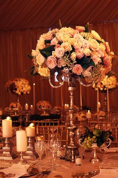 A tall, ornate wedding centerpiece allows guests to speak freely across the banquet table.