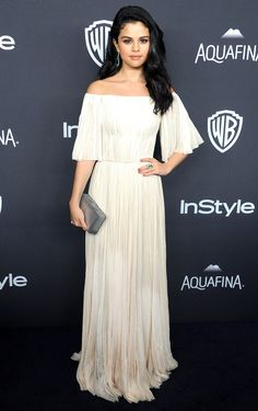 Selena Gomez looked every inch the ethereal goddess in a flowing white pleated gown with flutter sleeves. She accessorized with a muted silver box clutch and Jimmy Choo heels. See more Golden Globes afterparty looks here!