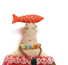 Textile cloth art doll with a bright coral fish on the top of her head