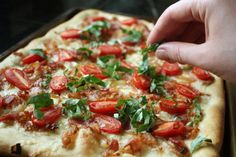 Pizza with Carmelized Onions, Bacon, Cherry Tomatoes, and Fontina - via Completely Delicious