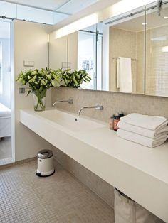 Baderomsinnredningen består av en lang benk, med dobbel vask. Under benken er det helt åpent, og her er det derfor plass til både søppelbøtte og skittentøyskurv. Skapplass finner du derimot bak speilene, som egentlig er skapdører. Gulvet og halve veggen er flisebelagt med beige mosaikk.