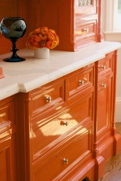 The Bold and The Beautiful: Traditional kitchen with orange lacquered cabinetry and Calacatta marble counters by BD Home Interiors.