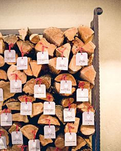 Escort Cards    Escort cards bearing crests with the couple's initials are nailed to a stack of firewood.