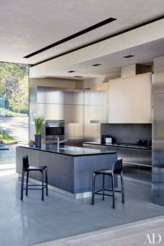 The interiors of director Michael Bay's Los Angeles residence were realized by designer Lorraine Letendre, with additional work by decorator Lynda Murray. The kitchen is outfitted with Boffi cabinetry and countertops and a Wolf wall oven and cooktop; the stools are by Matteograssi.