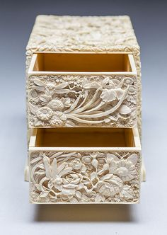 JAPANESE CARVED IVORY BOX, MEIJI PERIOD (1868-1912) The two removable drawers carved all over with flowers and butterflies, one side panel carved in low relief with three figures, the other four men and a cart; signed.  Dimensions: Height 5 1/4 in. (13.3 cm.)