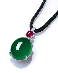 A highly important jadeite, ruby and diamond pendant necklace. Estimate HK$28,000,000 – HK$38,000,000 ($3,500,000-4,800,000). Suspending a thick high-domed jadeite cabochon of vivid emerald green colour and high translucency, surmounted by a cabochon ruby and a brilliant-cut diamond spacer, to the length adjustable black cord, mounted in 18k white gold,cabochon approximately 26.1 x 21.3 x 14.5 mm, 63.5 cm long