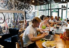 Will Levandowski and Cecie Levandowski study at the Denver Bicycle Cafe on Aug. Denver Bicycle Cafe opened in 2011 and combines a cafe and bar with a full service bike repair shop. Bicycle Cafe, Bicycle Store, Cafe Display, Dyi, Shop Storage, Bike Design, Store Design, Bike Shops, Mountain Biking