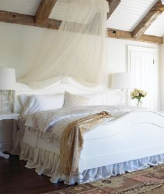 Dreamy Country Bedroom ~~~  A beamed ceiling and white panelling offer a classic country look.
