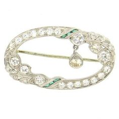 Delicate Art Deco platinum brooch, decorated with emeralds and diamonds. Weight of the piece - 7.2 grams DESIGNER: Not Signed MATERIAL: Platinum GEMSTONE: Diamond DIMENSIONS: Brooch measures 41mm x 24