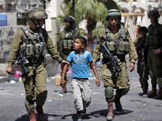 Israeli soldiers detain a young Palestinian boy following clashes in the centre of the West Bank town of Hebron, on June 20, 2014. A 13-year-old West Bank Palestinian was killed as Israeli soldiers pressed a crackdown on the Islamist movement Hamas.