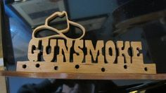 In the old West, if you were fast enough on the trigger and lucky to be alive, you could smell the Gunsmoke in the air. The cowboy fast enough to fill the air with gunsmoke was the lucky winner. This sign represents this image from the past, riddled with bullet holes. Hand cut from 1/2 cherry and mounted on a custom base of sapele, this piece will make a nice addition to a bookshelf, home bar, desktop, or childrens room. No stain was needed. The beauty of the wood grain is forced to the...