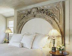 Creative Headboard That Imitates A Fireplace - Large arch design covers the whole section of the wall casting a royal look on this bedroom.