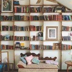 Handmade floor to ceiling bookshelf filled with antique books. Have your own Beauty and the Beast library room!