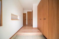 右に木目が美しい玄関収納 その扉はLIXILのウッディライン、クリエラスクです。左にはラインニッチ