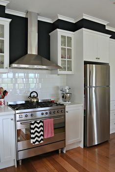 I am loving the commercial oven, white wood, black walls, crown moulding, gray ceiling...ALL of it! Add a splash of color with accessories and change it out easily.